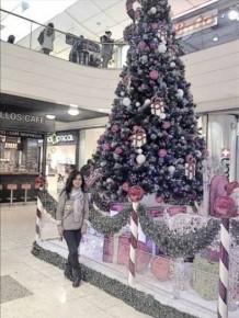 פיליפינית נוצרייה מצטלמת לצד עץ אשוח שהוצב בקניון בתל אביב